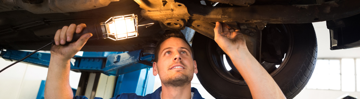 Mechanics checking and servicing a vehicle - Car Servicing Kirkby